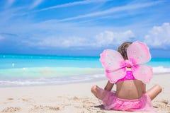 有蝴蝶的逗人喜爱的小女孩飞过海滩假期 免版税库存图片