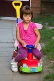 有蝴蝶翼的小女孩获得乐趣在汽车玩具 免版税图库摄影