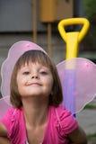 有蝴蝶翼的小女孩获得乐趣在汽车玩具 免版税库存照片