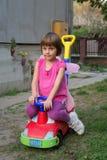 有蝴蝶翼的小女孩获得乐趣在汽车玩具 免版税库存图片