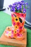 有蝴蝶花的胶靴 免版税库存照片