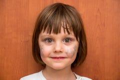 有蝴蝶面孔油漆的小女孩 免版税库存图片
