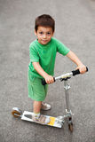 有滑行车的愉快的男孩 免版税图库摄影