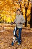 有滑行车的男孩在10月公园 免版税库存照片