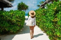 有去袋子和太阳的帽子的妇女靠岸 库存照片