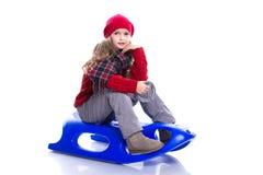 有戴被编织的毛线衣、围巾和帽子的卷曲发型的微笑的小女孩坐雪撬,隔绝在白色 库存图片