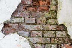有破裂的膏药的砖墙 图库摄影