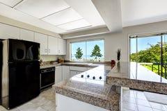 有黑装置和花岗岩上面的白色厨房室 免版税库存照片