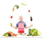 有围裙的一个男孩玩杂耍与菜的,当准备沙拉时 图库摄影