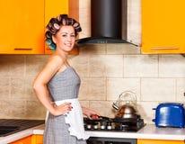 有围裙的中间年龄妇女在厨房里 库存照片
