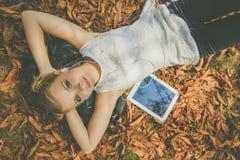 有说谎在叶子的数字式片剂的青少年的女孩 免版税库存照片