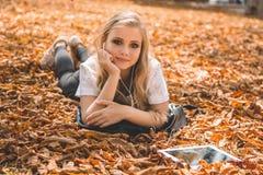 有说谎在叶子的数字式片剂的青少年的女孩 库存照片