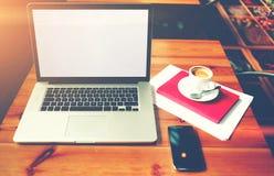 有说谎在咖啡馆,距离工作的一张桌上的手机的便携式计算机通过互联网 免版税库存照片