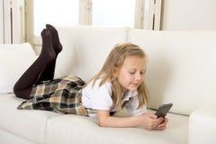 有说谎在家庭沙发的金发的女孩使用手机的互联网app 图库摄影