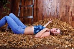 有说谎在干草的长的金发的美丽的女孩 库存图片