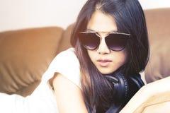 有说谎在沙发的太阳镜的亚裔妇女 免版税库存照片