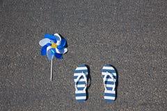 有说谎在沥青的轮转焰火的海滩拖鞋 库存图片