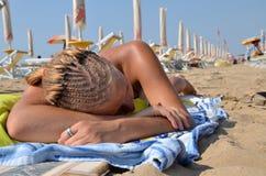 有说谎在海滩的猪尾的女孩 免版税库存图片