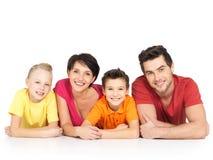 有说谎在白色地板上的两个孩子的愉快的家庭 免版税库存图片