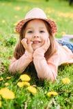 有说谎在草的帽子的小女孩 免版税库存图片