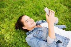 有说谎在草的智能手机的微笑的女孩 免版税库存图片