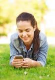 有说谎在草的智能手机的微笑的女孩 免版税库存照片