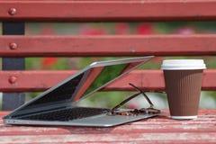 有说谎在长凳的玻璃和笔记本的膝上型计算机在城市公园,室外研究或者互联网自由职业者的运作的概念 免版税库存照片