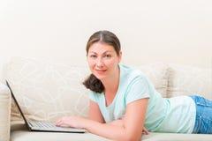 有说谎在长沙发的膝上型计算机的妇女 免版税库存图片