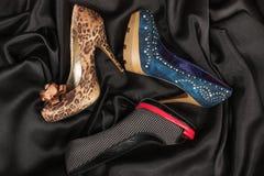 有说谎在黑丝绸的高跟鞋的三双豪华妇女` s鞋子 免版税库存图片