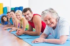 有说谎在锻炼席子的朋友的资深妇女在健身房 免版税库存照片
