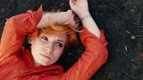 有说谎黑地球上的红色头发的哀伤的女孩,哀伤地凝视天空 概念:需要帮助,寂寞 影视素材