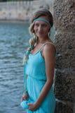 有结辨的年轻白肤金发的妇女听见佩带的绿松石礼服 图库摄影