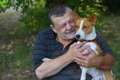 有他逗人喜爱的狗的有胡子的老人 免版税库存图片