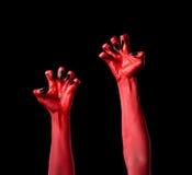 有黑钉子的红魔手,真正的身体艺术 库存照片