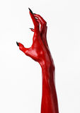 有黑钉子的红魔的手,撒旦,万圣夜题材的红色手,在白色背景,被隔绝 免版税库存图片