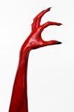 有黑钉子的红魔的手,撒旦,万圣夜题材的红色手,在白色背景,被隔绝 库存照片