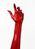 有黑钉子的红魔的手,撒旦,万圣夜题材的红色手,在白色背景,被隔绝 免版税图库摄影