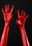 有黑钉子的红魔的手,撒旦,万圣夜题材的红色手,在黑背景,被隔绝 库存图片
