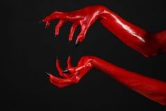 有黑钉子的红魔的手,撒旦,万圣夜题材的红色手,在黑背景,被隔绝 库存照片