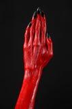 有黑钉子的红魔的手,撒旦,万圣夜题材的红色手,在黑背景,被隔绝 免版税库存图片