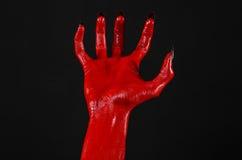 有黑钉子的红魔的手,撒旦,万圣夜题材的红色手,在黑背景,被隔绝 免版税库存照片