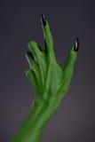 有黑钉子的绿色巫婆手,真正的身体艺术 库存图片