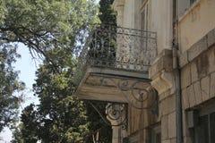 有锻铁栏杆的阳台在老被毁坏的墙壁特写镜头扭转了 免版税库存照片