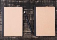 有黑铅笔的两个空白的棕色笔记本 免版税图库摄影