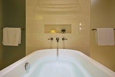 有黄铜轻拍的被填装的白色浴缸在大理石墙壁和阵雨屏幕登上了在双方 免版税图库摄影