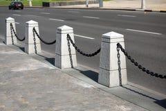 有黑链子的石篱芭在都市路附近的一个城市在夏日 免版税库存照片