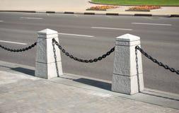 有黑链子的石篱芭在都市路附近的一个城市 库存图片