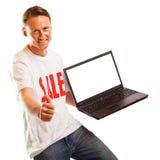 有`销售` T恤杉和膝上型计算机的年轻人 免版税库存照片