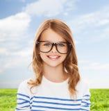 有黑镜片的微笑的逗人喜爱的小女孩 免版税库存图片