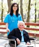 有年长夫人的In Wheelchair亲切的护士 免版税库存照片